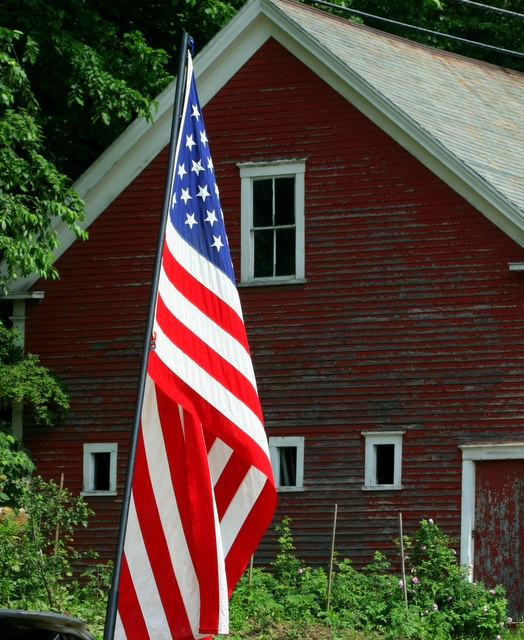 Red barn and American flag in New Boston village...