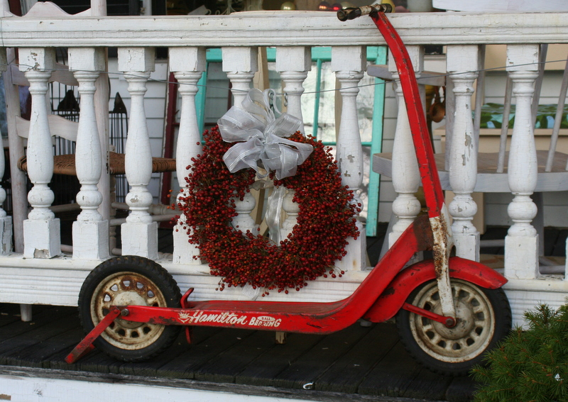 Scooter and wreath outside antique shop...
