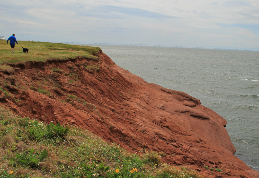 Steve, Lucy & the red cliffs of Seacow Head Lighthouse with the Confederation Bridge in the distance