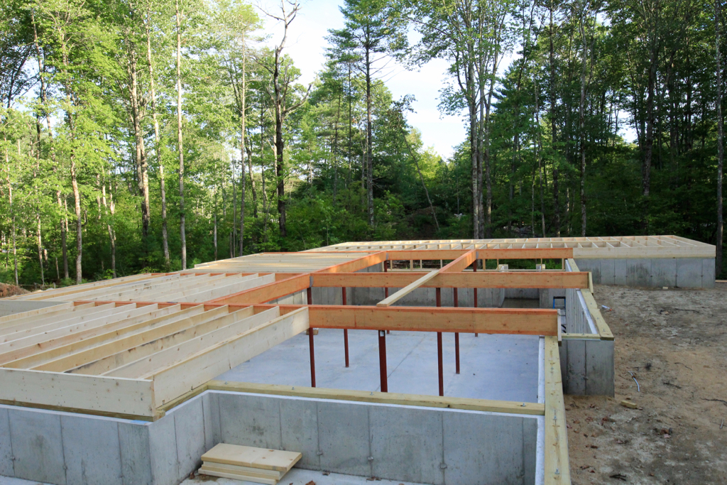 Basement slab is poured, carrying beams are up and framing is finally underway!